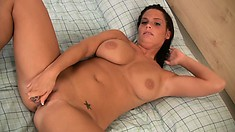 Stacked hottie Whitney lies on the bed pleasing her wet snatch with a sex toy