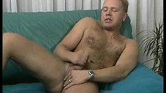 Hairy hunk lies fully naked on the couch and strokes his big dick