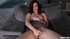 Hot redhead girl sits on the sofa and plays with her tiny tits and wet snatch