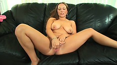 Buxom brunette babe sits on the couch and strips to finger her twat